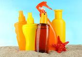 Bottles with suntan cream, on blue background — Stock Photo