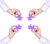 Four hands holding colorful puzzle, isolated on white — Stock Photo