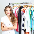 Stock Photo: Beautiful young stylist near rack with hangers