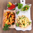 French fries and home potatoes on tracing paper on board on wooden table — Stock Photo