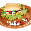 Stock Photo: Conceptual image for nutritional care:assorted vitamins and nutritional supplements in bun.Isolated on white