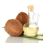 Decanter with coconut oil and coconuts isolated on white — Stock Photo