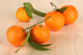Sweet tangerines with leaves, on wooden background — Stock Photo