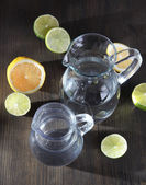 Dzbany szklankę wody na drewniany stół szczegół — Zdjęcie stockowe