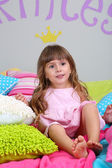 Little girl sitting on bed in room on grey wall background — Stok fotoğraf