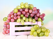 Ripe green and purple grapes in wooden box on wooden table on natural background — Stock Photo
