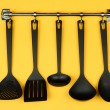 Stock Photo: Black kitchen utensils on silver hooks, on yellow background