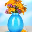 Stock Photo: Bouquet of marigold flowers in vase on wooden table on natural background