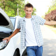 Man on road with car breakdown trying to stop car — Stockfoto