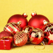 Christmas balls and small gift on yellow background — Stock Photo #31293103