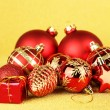 Christmas balls and small gift on yellow background — Stock Photo