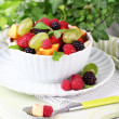 Fruit salad in bowl, on wooden table, on bright background — Stock Photo