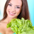 Beautiful girl with fresh salad on blue background — Stock Photo