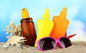 Bottiglie con abbronzatura crema e occhiali da sole, su sfondo blu — Foto Stock