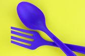 Plastic kitchen utensils on yellow background — Stock Photo