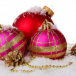 Foto Stock: Beautiful pink and red Christmas balls and cones on snow isolated on white