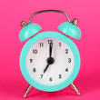 Blue alarm clock on pink background — Stock Photo
