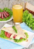 Composition with fruit juice and tasty sandwich with salami sausage and vegetables on color napkin, on wooden table background — Stock Photo