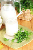 Fresh yogurt with greens on wooden table on natural background — Stock Photo