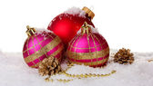 Beautiful pink and red Christmas balls and cones on snow isolated on white — Zdjęcie stockowe