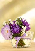 Hermoso ramo de flores en florero de cristal, sobre una mesa de madera, sobre fondo brillante — Foto de Stock