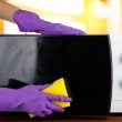 Hand with sponge cleaning microwave oven, on bright background — Stock Photo #31515997