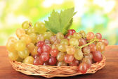 Ripe sweet grape on wooden table, on nature background — Stock Photo