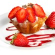 Tasty muffin cake with strawberries and chocolate on plate, isolated on white — Stock Photo