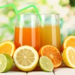 Lots ripe citrus with juices on wooden table on natural background — Stock Photo