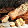 Much bread on wooden board on wicker tray background — Stock Photo