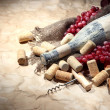 Stock Photo: Old bottle of wine, grapes and corks on old paper background
