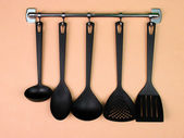 Black kitchen utensils on silver hooks, on peach background — Stock Photo