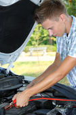 Young driver uses battery jumper cables to charge dead battery — Stock Photo