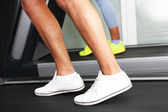 Women and men feet on treadmill close-up — Stock Photo