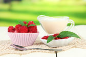 Fresh raspberry, raspberry jam and cream in jug on wooden table, on bright background — Stock Photo