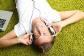 Ung man koppla på mattan och lyssna på musik — Stockfoto
