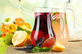 Red basil lemonade in jug and glass, on wooden table, on bright background — Стоковое фото