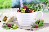 Fruit salad in cup on wooden table on nature background — Stock Photo