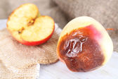 Rotten apples on wooden board on sackcloth — Stock Photo