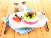 Colored rice on plate on napkin on wooden table — Stock Photo