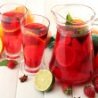 Sangria in jar and glasses with fruits, on white wooden table — Stock Photo #31598625
