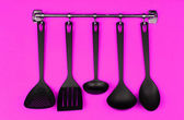Black kitchen utensils on silver hooks, on pink background — Stock Photo
