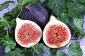 Ripe figs in leaves on wooden table close-up — Stock Photo