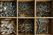 Wooden box for metal bolts, screws and nuts close up — Stock Photo