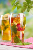 Iced tea with raspberries, lemon and mint on wooden table, outdoors — Zdjęcie stockowe