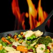 Casserole with vegetables and meat on pan, on fire background — Stock Photo #31720429