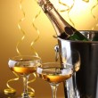 Stock Photo: Champagne bottle in bucket with ice and glasses of champagne, on yellow background