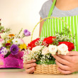 Florist makes flowers bouquet in wicker basket — Stock Photo #31729627