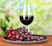 Ripe grapes and glass of wine, on bright background — Stock Photo