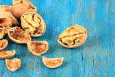 Broken walnuts on wooden table close-up — Stock Photo